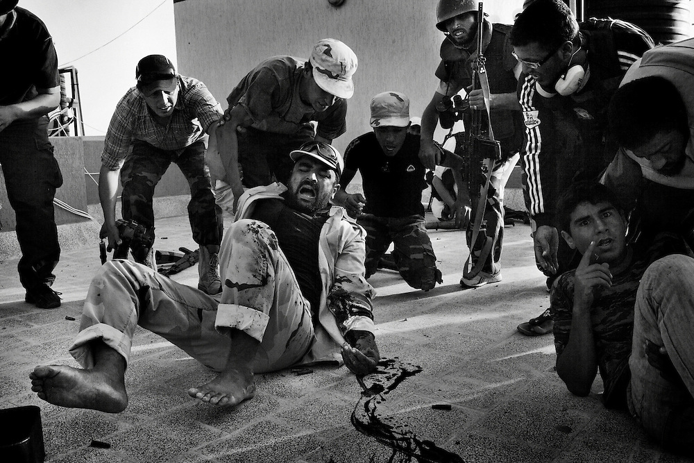 An anti-Qaddafi fighter (L) falls on the ground after being shot on the left arm, seconds after a young man (R) being hit on the chest by loyalists to Col. Muammar el-Qaddafi during a heavy gun battle atop of a residential building from the east end for Qaddafi's hometown city of Sirte, Libya, on October 9, 2011. Photo by Mauricio Lima for The New York Times