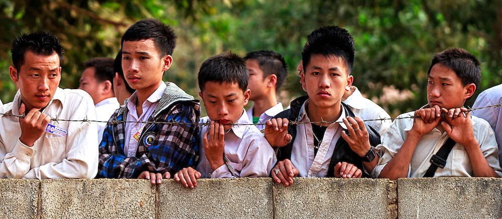 Male teenagers are kept behind a brick wall topped with barbed wire, await the morning school bell Nong Khiaw, a quiet town in Laos and exhibit all the pensive anguish seen in youth the world over.