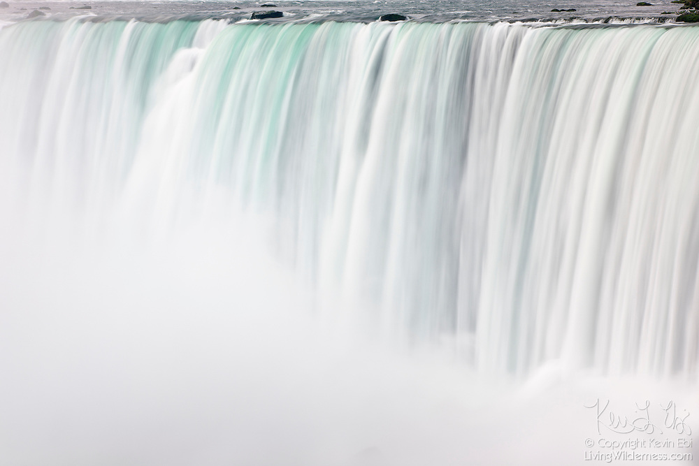 Falling water vanishes into a cloud of mist at Horseshoe Falls, one of the waterfalls that make up Niagara Falls on the border of New York and Ontario. About 90 percent of the water in the Niagara River flows over Horseshoe Falls, which amounts to about 600,000 gallons (2.3 million liters) of water per second. The waterfall is about a half-mile wide, with a brink length of 2600 feet (792 meters), and it is 167 feet (51 meters) high. Horseshoe Falls is also known as Canadian Falls, since about two-thirds of it is located in Canada.