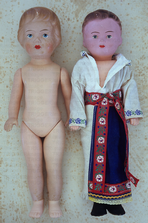 Vintage female doll with face slightly freckled from ageing lying naked on antique paper next to boy doll wearing kimono and shoes