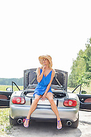 Thoughtful woman sitting on convertible trunk against clear sky