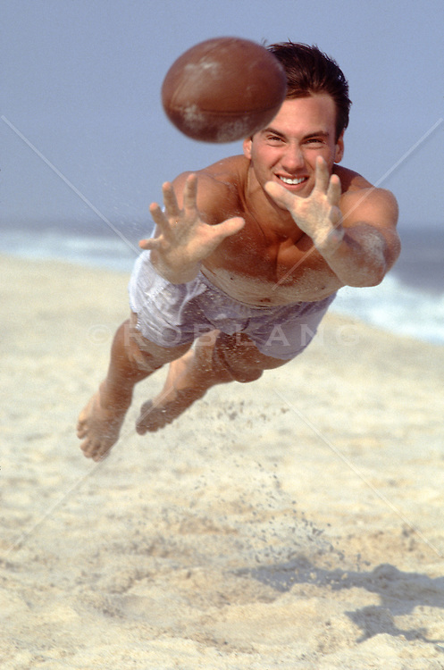 man on the beach catching a football in midair