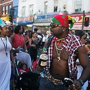 A man in a bandana, customized ripped shirt and a lot of bling dances along with the procession up the high street in East London, United Kingdom,Sept 11 2016.The annual Hackney Carnival took place on a hot summers day and the procession of dancers dressed in various outfits moved through the streets to much joy of the many bystanders.