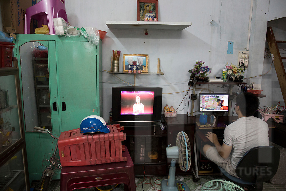 Vietnamese man plays online games in a dwelling of a  low-income neighbourhood, Ho Chi Minh City, Vietnam, Southeast Asia