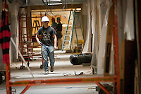 JEROME A. POLLOS/Press..Thomas Cheevers, a worker with All Wall Construction, walks down the north corridor of Lakes Magnet Middle School as he prepares to leave the construction site for the day Thursday.