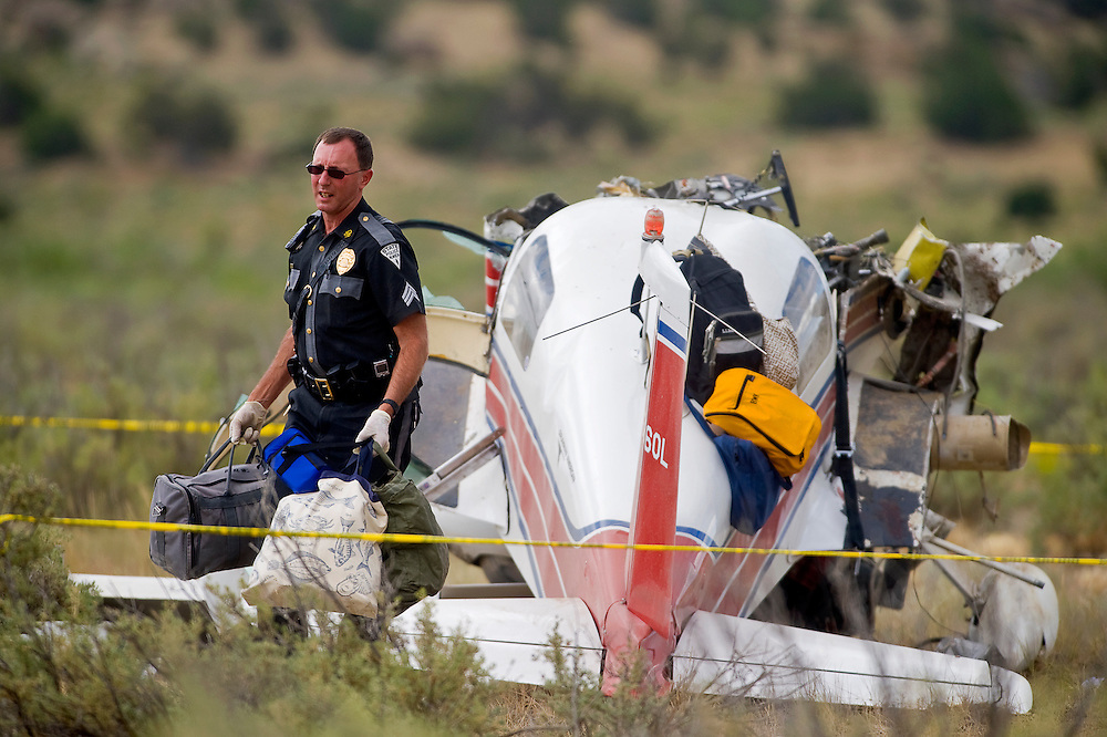 071910      Brian Leddy.New Mexico State Police Sgt. Rod Huffman carries baggage from an airplane that crashed in a vacant field on Monday morning. The airplane crashed after attempting to land at the Gallup airport for fuel.