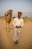 A portrait of a camel driver with red turban walking in the sand, Pushkar, India