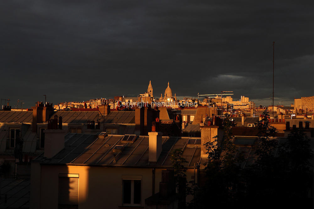 Parisian rooftop view at dusk with Montmartre Hill and Basilique du Sacre Coeur silhouetted beneath a stormy sky, Paris, France. Picture by Manuel Cohen