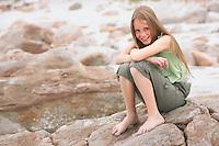 Girl (10-12) sitting on rock on beach portrait