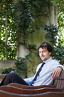 Businessman sitting on park bench relaxing portrait