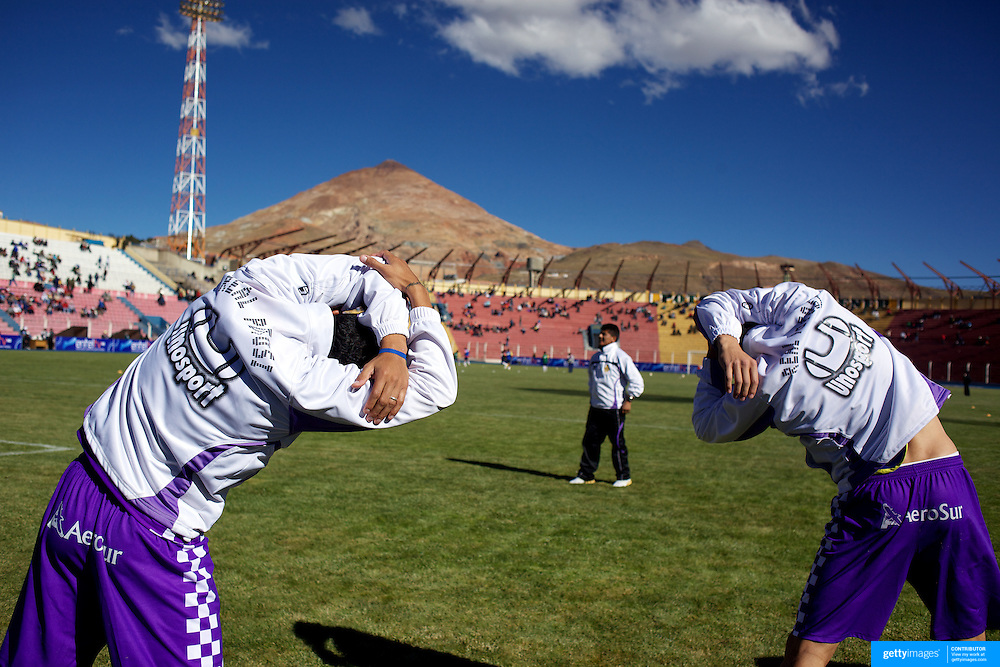 'Attitude at Altitude' Football in Potosi, Bolivia'..The Real Potosi team warm up before the match between Real Potosi and Wilstermann at the The Estadio Victor Agustin Ugarte, Potosi, Bolivia, Real Potosi won the match 3-0. 2nd May 2010. Photo Tim Clayton..'Attitude at Altitude' Football in Potosi, Bolivia'..The Calvario players greet the final whistle with joyous celebration, high fives and bear hugs the players are sprayed with local Potosina beer after a monumental 3-1 victory over arch rivals Galpes S.C. in the Liga Deportiva San Cristobal. The Cup Final, high in the hills over Potosi. Bolivia, is a scene familiar to many small local football leagues around the world, only this time the game isn't played on grass but a rock hard earth pitch amongst gravel and boulders and white lines that are as straight as a witches nose, The hard surface resembles the earth from Cerro Rico the huge mountain that overlooks the town. .. Sitting at 4,090M (13,420 Feet) above sea level the small mining community of Potosi, Bolivia is one of the highest cities in the world by elevation and sits 'sky high' in the hills of the land locked nation. ..Overlooking the city is the infamous mountain, Cerro Rico (rich mountain), a mountain conceived to be made of silver ore. It was the major supplier of silver for the spanish empire and has been mined since 1546, according to records 45,000 tons of pure silver were mined from Cerro Rico between 1556 and 1783, 9000 tons of which went to the Spanish Monarchy. The mountain produced fabulous wealth and became one of the largest and wealthiest cities in Latin America. The Extraordinary riches of Potosi were featured in Maguel de Cervantes famous novel 'Don Quixote'. One theory holds that the mint mark of Potosi, the letters PTSI superimposed on one another is the origin of the dollar sign...Today mainly zinc, lead, tin and small quantities of silver are extracted from the mine by over 100 co operatives and private mining companies who still min