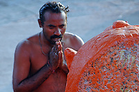 India, Nasik, 2006. After his ritual cleansing, a pilgrim prays before one of the many Hindu gods that line the Ramkund, or holy reservoir, in Nasik.