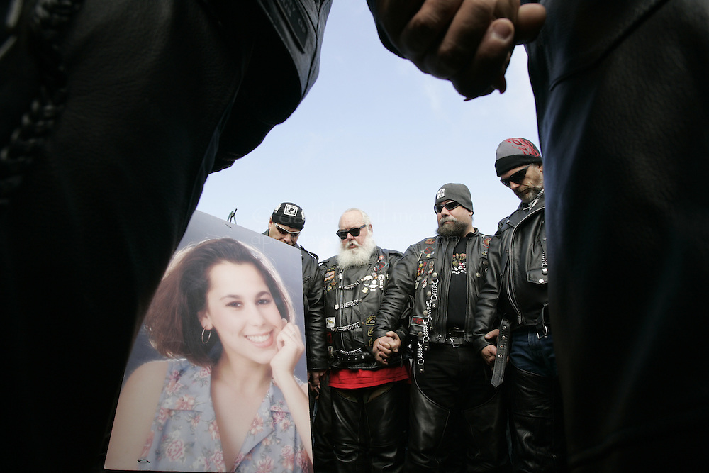 Modesto, CA - NOVEMBER 20: Friends and family members of Laci Peterson  pray during a brief stop at the Burwood Cemetery in Escalon where Laci Peterson is buried in Escalon, California. Over 2,000 people take part in the second annual Laci Peterson Memorial Motorcycle ride in Modesto, California on Saturday November 20, 2004. Laci was murdered along with her unborn son, Conner in December 2002 by her husband Scott Peterson who was found guilty of  first degree of murder by a San Mateo, California jury on November 12, 2004 and could face the death penalty. Photograph by David Paul Morris