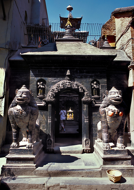Kathmandu, Patan, Golden Temple during Dasain holiday, 2001.  Facade and entrance gate, frontal view.  Two guardian lion sculptures, one on either side of the approach. Figure on the right has female breasts painted a vivid orange. Bhaskerdev Samskarita Hiranyabarna Mahavihara: A Buddhist temple known locally as Golden Temple, located in the Durbar Square monument zone of the Kathmandu Valley.