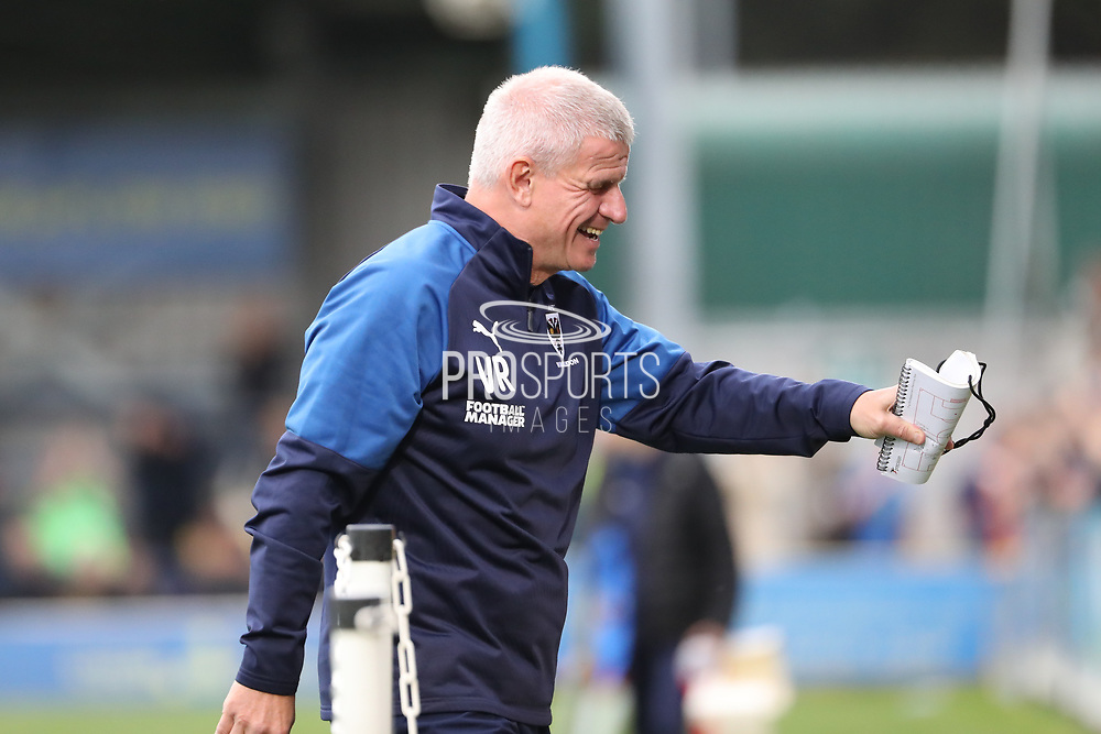 AFC Wimbledon coach Vaughan Ryan holding notebook and walking off the pitch laughing during the EFL Sky Bet League 1 match between AFC Wimbledon and Rochdale at the Cherry Red Records Stadium, Kingston, England on 5 October 2019.