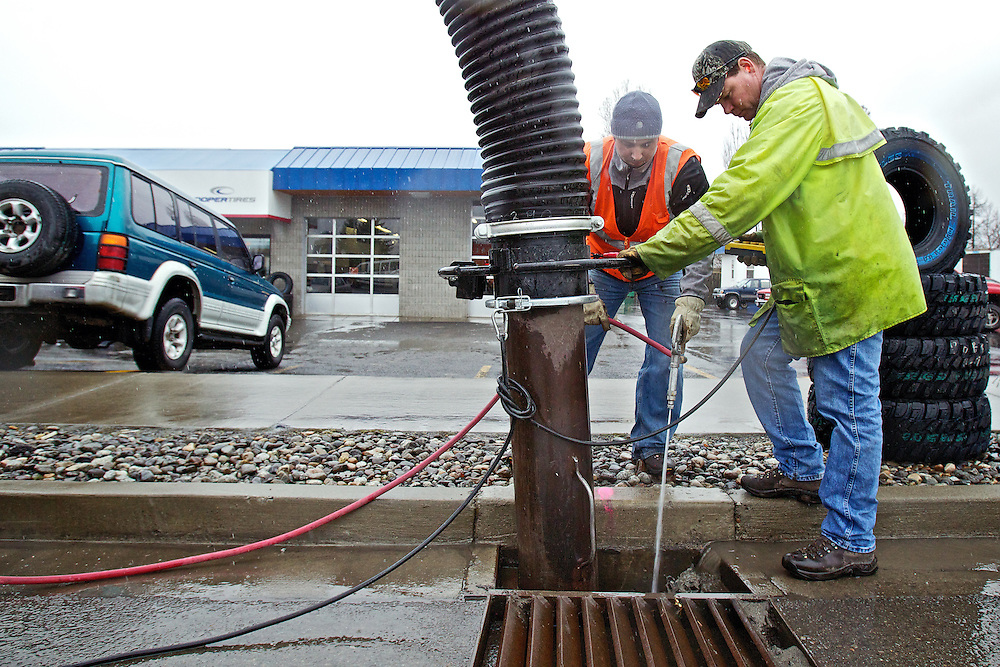 Coeur d'Alene Street Department employees Aman Sterling, left, and Eric Killen, clear a storm water drain on Government Way during a steady rain Thursday.