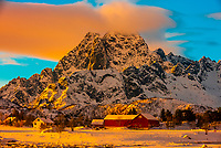 Houses surrounded by snow covered mountains, Austvagoya Island, Lofoten Islands, Arctic, Northern Norway.