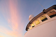 Low angle view of the sunrise reflecting in the windows of the bridge of a small cruise ship in Alaska.