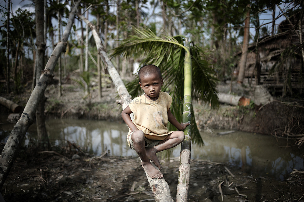 A young girl sits on a tree in her village of Chaung Lin on May 23, 2008 in the isolated area of Kanzeik in the Irrawaddy Delta region -- an area only accessible by boat which has received neither government nor foreign aid.  Voters in regions devastated by the cyclone, many hungry and destitute, cast ballots on May 24 in a referendum that many said was meaningless because Myanmar's junta has already declared victory.