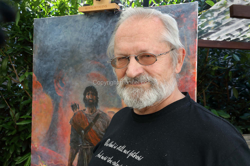 Portrait of Grzegorz Rosinski, Polish comic book artist, born 1941 in Stalowa Wola, Poland, in the garden of his house in Mollens, Sierre, Switzerland, 9th September 2016. Rosinski is the author and designer of many Polish comic book series, and created Thorgal with Belgian writer Jean Van Hamme in 1977. Here, he stands in front of a painting from the Thorgal series in his outdoor studio area on a verandah in his garden. The stories cover Norse mythology, Atlantean fantasy, science fiction, horror and adventure genres. Picture by Manuel Cohen