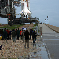 Members of the press take final photos in the rain as Shuttle Atlantis rests atop the launch pad at Kennedy Space Center Thursday, July 7, 2011, in Cape Canaveral, Fla. Shuttle Atlantis is scheduled to launch on Friday, July 8 and is the 135th and final space shuttle launch for NASA..  (AP Photo/Alex Menendez)