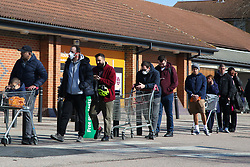 © Licensed to London News Pictures. 22/03/2020. London, UK. Shoppers wearing face masks queue at a Sainsbury's in Harringay, north London before the store opens, as the spread of the Coronavirus continues in the capital. Photo credit: Dinendra Haria/LNP