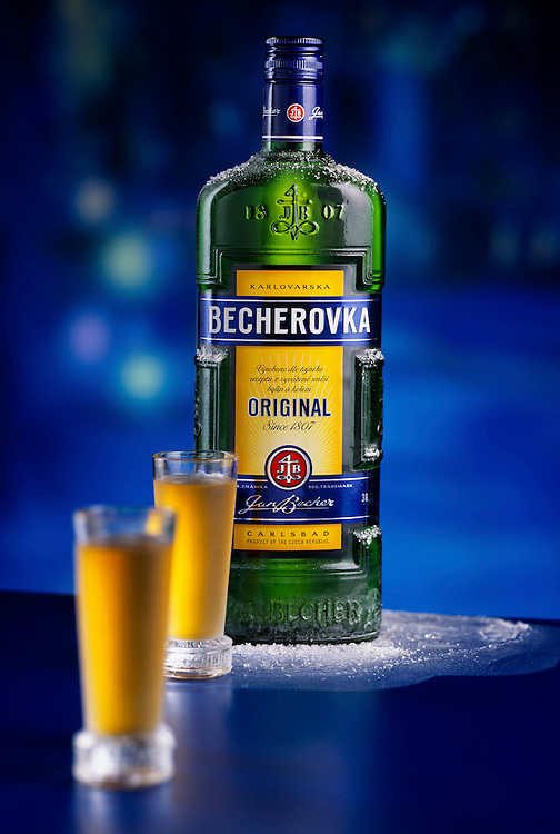 Becherovka original beauty bottle and glasses on a surface of ice against a blue background Ray Massey is an established, award winning, UK professional  photographer, shooting creative advertising and editorial images from his stunning studio in a converted church in Camden Town, London NW1. Ray Massey specialises in drinks and liquids, still life and hands, product, gymnastics, special effects (sfx) and location photography. He is particularly known for dynamic high speed action shots of pours, bubbles, splashes and explosions in beers, champagnes, sodas, cocktails and beverages of all descriptions, as well as perfumes, paint, ink, water – even ice! Ray Massey works throughout the world with advertising agencies, designers, design groups, PR companies and directly with clients. He regularly manages the entire creative process, including post-production composition, manipulation and retouching, working with his team of retouchers to produce final images ready for publication.