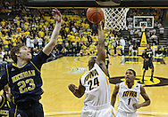 February 19 2011: Iowa Hawkeyes guard Bryce Cartwright (24) puts up a shot over Michigan Wolverines forward Evan Smotrycz (23) as Iowa Hawkeyes forward Melsahn Basabe (1) looks on during the first half of an NCAA college basketball game at Carver-Hawkeye Arena in Iowa City, Iowa on February 19, 2011. Michigan defeated Iowa 75-72 in overtime.