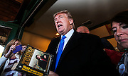 Republican presidential candidate Donald Trump autographs a book on his way out after speaking at a town hall meeting at the Atkinson Country Club in Atkinson, N.H., Monday, Oct. 26, 2015.  (AP Photo/Cheryl Senter)