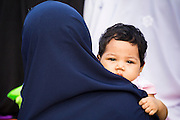 28 JULY 2014 - KHLONG HAE, SONGKHLA, THAILAND: A woman holds her child during Eid services at Songkhla Central Mosque in Songkhla province of Thailand. Eid al-Fitr is also called Feast of Breaking the Fast, the Sugar Feast, Bayram (Bajram), the Sweet Festival and the Lesser Eid, is an important Muslim holiday that marks the end of Ramadan, the Islamic holy month of fasting.  PHOTO BY JACK KURTZ