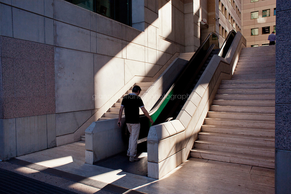 Reggio Calabria, Italy - 31 August, 2012: A man walks up the escalator of the Courthouse in Reggio Calabria, Italy, on August 31, 2012. The Libri gang of Reggio Calabria has managed to infiltrate even the construction of the new palace of justice, not through the traditional system of bribes, but by legally signing for the delivery of services and labor that was controlled and taxed by the mob.<br /> <br /> Calabria is one of the poorest Italian regions which suffers from lack of basic services (hospitals without proper equipment, irregular electricity and water), the product of disparate political interests vying for power. The region is dominated by the 'Ndrangheta (pronounced en-Drang-get-A), which authorities say is the most powerful in Italy because it is the welthiest and best organized.<br /> <br /> The region today has nearly 20 percent unemployment, 40 percent youth unemployment and among the lowest female unemployment and broadband Internet levels in Italy. Business suffer since poor infrastructure drives up transport costs.<br /> <br /> Last summer the European Union's anti-fraud office demanded that Italy redirect 380 million euros in structural funding away from the A3 Salerno - Reggio Calabria highway after finding widespread evidence of corruption in the bidding processes.