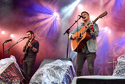 """© Licensed to London News Pictures. 22/07/2017. London, UK. Kevin McGuire performs on stage.  """"Nashville Meets London"""", a country music festival, takes place in Canary Wharf.  Heavy rain fails to dampen the enjoyment of dedicated country music fans, many wearing protective ponchos, watching artists from the UK as well as the USA for the two day weekend festival. Photo credit : Stephen Chung/LNP"""