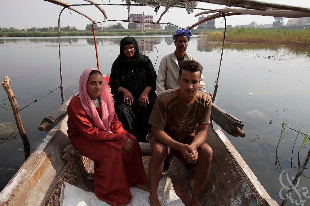 Egyptian fisherman Mahrouz Ahmed (back-right, age 49), his wife Om Hassan Suleyman (back-left, age 47)  daughter in law Reda Ahmed Al Ibrahim (front-l, age 27 and Abdel Hamid Mahrouz front-r) sit inside their fishing boat on the banks of the Nile river October 27, 2011 in the village of Warwara, near the delta town of Benha, about 50 kilometers north of the capital, Cairo. Fisherman in Warwara say that since the recent revolution, the Egyptian government has stopped stocking the Nile with fingerlings, and their livelihoods are now being effected.  (Photo by Scott Nelson)