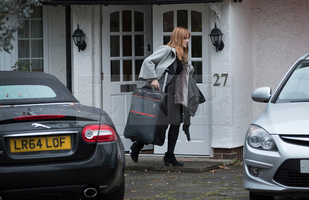 © Licensed to London News Pictures. 04/11/2017. London, UK. An unidentified woman is seen carrying a suitcase leaving a house in  Wimbledon where a seven year old girl was found seriously injured on Friday who has since died. Robert Peters appeared at Wimbledon Magistrates' Court on Saturday and was charged with attempted murder.  Photo credit: Peter Macdiarmid/LNP