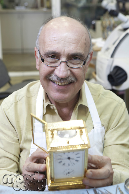 Portrait of a happy skilled worker with clock in repair shop