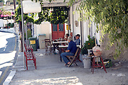 People sit outside local village taverna, Siana, Rhodes, Greece