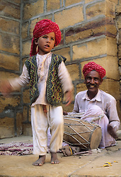 Asia, India, Jaisalmer, boy dancing while father plays drum at entrance to Jaisalmer fort