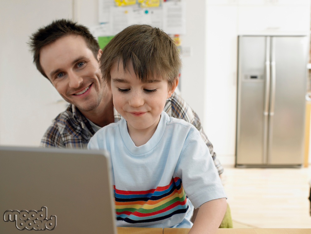Boy (3-6) using laptop with father at home (portrait)