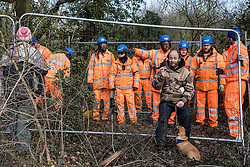Harefield, UK. 7 February, 2020. An activist leans on Heras fencing being erected by HS2 engineers to surround three environmental activists from Extinction Rebellion who have climbed a veteran oak tree close to the Harvil Road wildlife protection camp in order to try to protect it from felling. HS2 are expected to try to fell large numbers of mature trees in the immediate vicinity over the weekend even though the high-speed rail link is still awaiting Boris Johnson's approval.