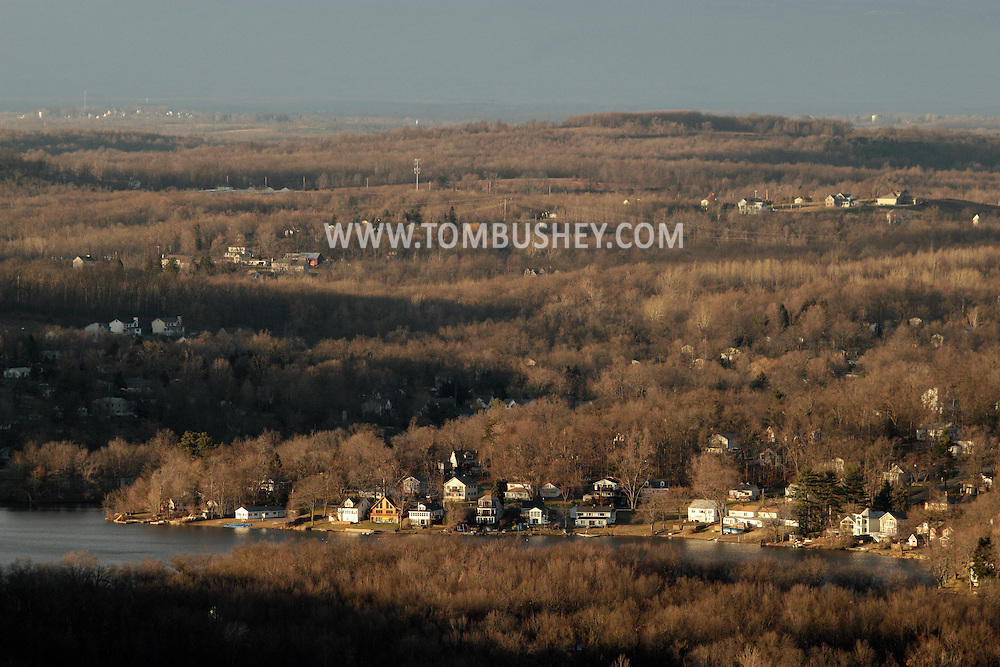 Salisbury Mills, New York - Houses on the shore of Beaverdam Lake, near the bottom of the frame, are lit by the setting sun in this view from Schunnemunk Mountain on Jan. 2, 2012.