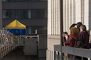 The morning after the terrorist attack at Fishmongers Hall on London Bridge, in which Usman Khan (a convicted, freed terrorist) killed 2 during a knife a attack, then subsequently tackled by passers-by and shot by armed police - tourists view the forensic tent where the killer was brought down, on 30th November 2019, in London, England, on 30th November 2019, in London, England.