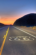 The setting sun provides a spectacular sky in distance with a Route 66 sign embedded in the pavement.