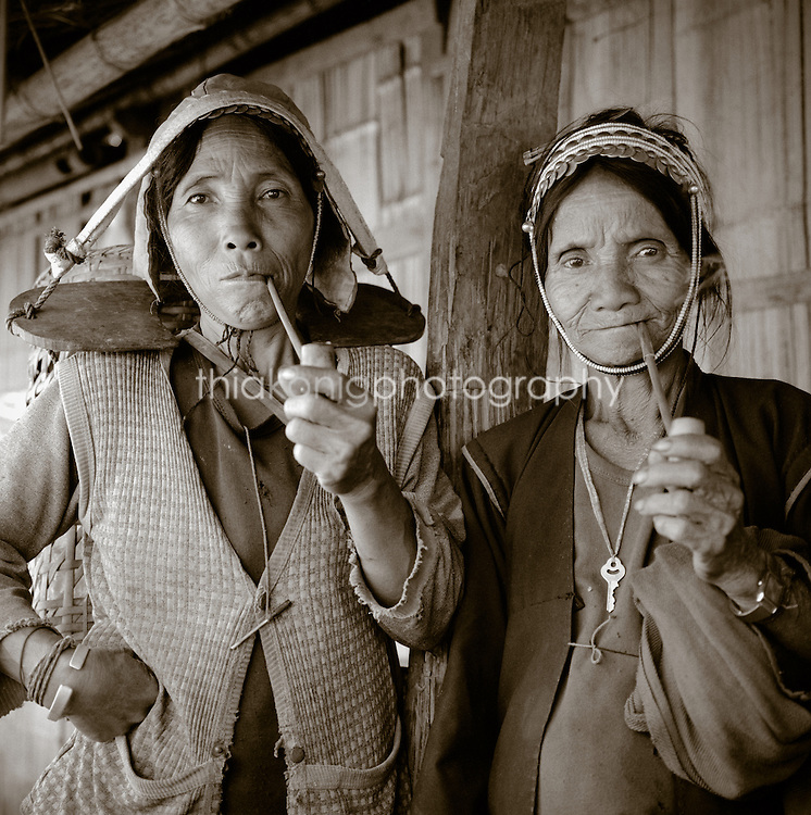 Two Ahka women smoke pipes, while wearing yokes for carrying firewood on thier heads. The Akha are an indigenous hill tribe that live in small villages at high altitudes in the mountains of Thailand, Burma, Laos, and China.