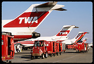 Man drives 'tug' & luggage carts beneath row of TWA jetliners at Lambert Intl Airport; St. Louis. Missouri