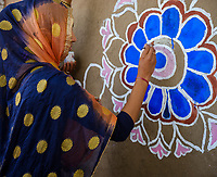 PUSHKAR, INDIA - CIRCA NOVEMBER 2018: Indian woman painting Indian designs during a contest in the Pushkar Camel Fair. It is one of the world's largest camel fairs. Apart from the buying and selling of livestock, it has become an important tourist destination. The city of Pushkar is a pilgrimage site for Hindus and Sikhs.
