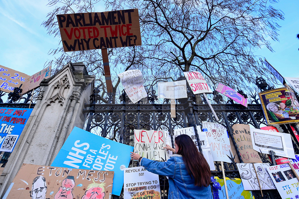 """© Licensed to London News Pictures. 23/03/2019. LONDON, UK.  Signs affixed to the railings of the Houses of Parliament after people took part in the """"Put It To The People March"""", on what was supposed to be six days before the UK was due to leave the EU, before an extension to the departure date was given.  Protesters demand that the public is given a final say on Brexit as support for the Prime Minister's withdrawal plan continues to recede.  Photo credit: Stephen Chung/LNP"""