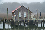 Old shingle sided boat house along Shem Creek on a foggy winter morning in Charleston, South Carolina.