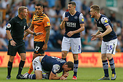 Hull City forward Josh Magennis (27) eyes the Referee Oliver Langford, as Millwall defender Murray Wallace (3) and Millwall defender Alex Pearce (15) demand a card is given after a foul on Millwall defender Jake Cooper (5) during the EFL Sky Bet Championship match between Millwall and Hull City at The Den, London, England on 31 August 2019.