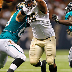 August 17, 2012; New Orleans, LA, USA; New Orleans Saints defensive end Akiem Hicks (76) rushes past Jacksonville Jaguars center Michael Brewster (60) during the second half of a preseason game at the Mercedes-Benz Superdome. The Jaguars defeated the Saints 27-24.  Mandatory Credit: Derick E. Hingle-US PRESSWIRE