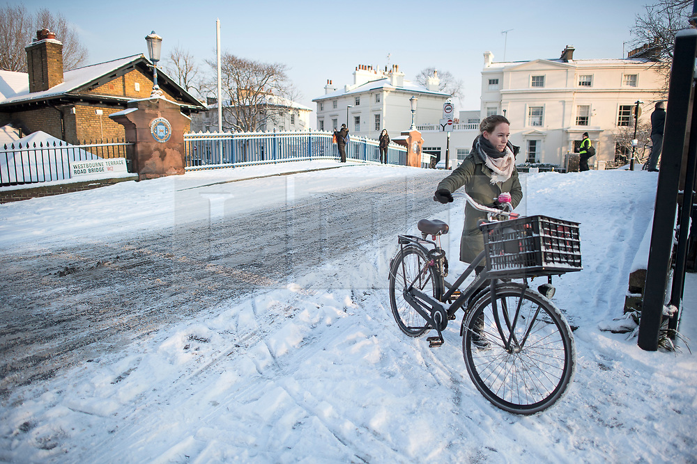 © Licensed to London News Pictures. 28/02/2018. London, UK. A woman is forced to push her bike over a bridge in Little Venice, West London following heavy snowfall last night. Large parts of the UK are experiencing disruption as 'Storm Emma' hits, following Russian a cold front earlier in the week named 'The Beast From The East'. Photo credit: Ben Cawthra/LNP